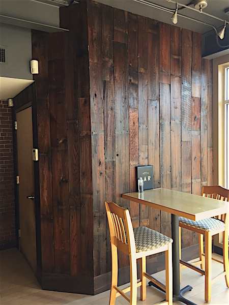 Accent wall in a restaurant in Portland, Maine featuring barn board sourced by Rousseau Reclaimed Lumber & Flooring