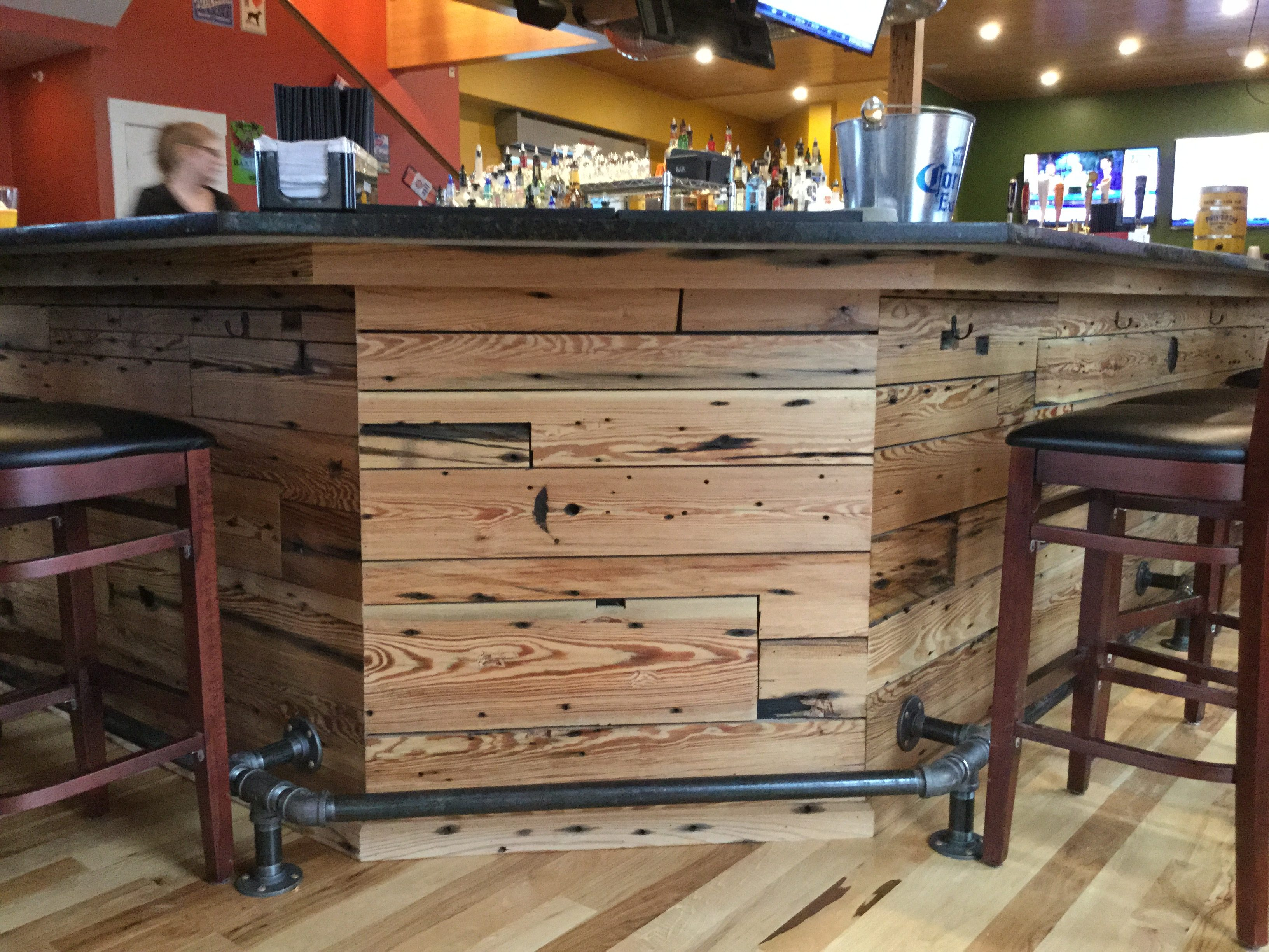 Angled bar in a restaurant in Portland, Maine, featuring reclaimed mill run heart pine sourced by Rousseau Reclaimed Lumber & Flooring