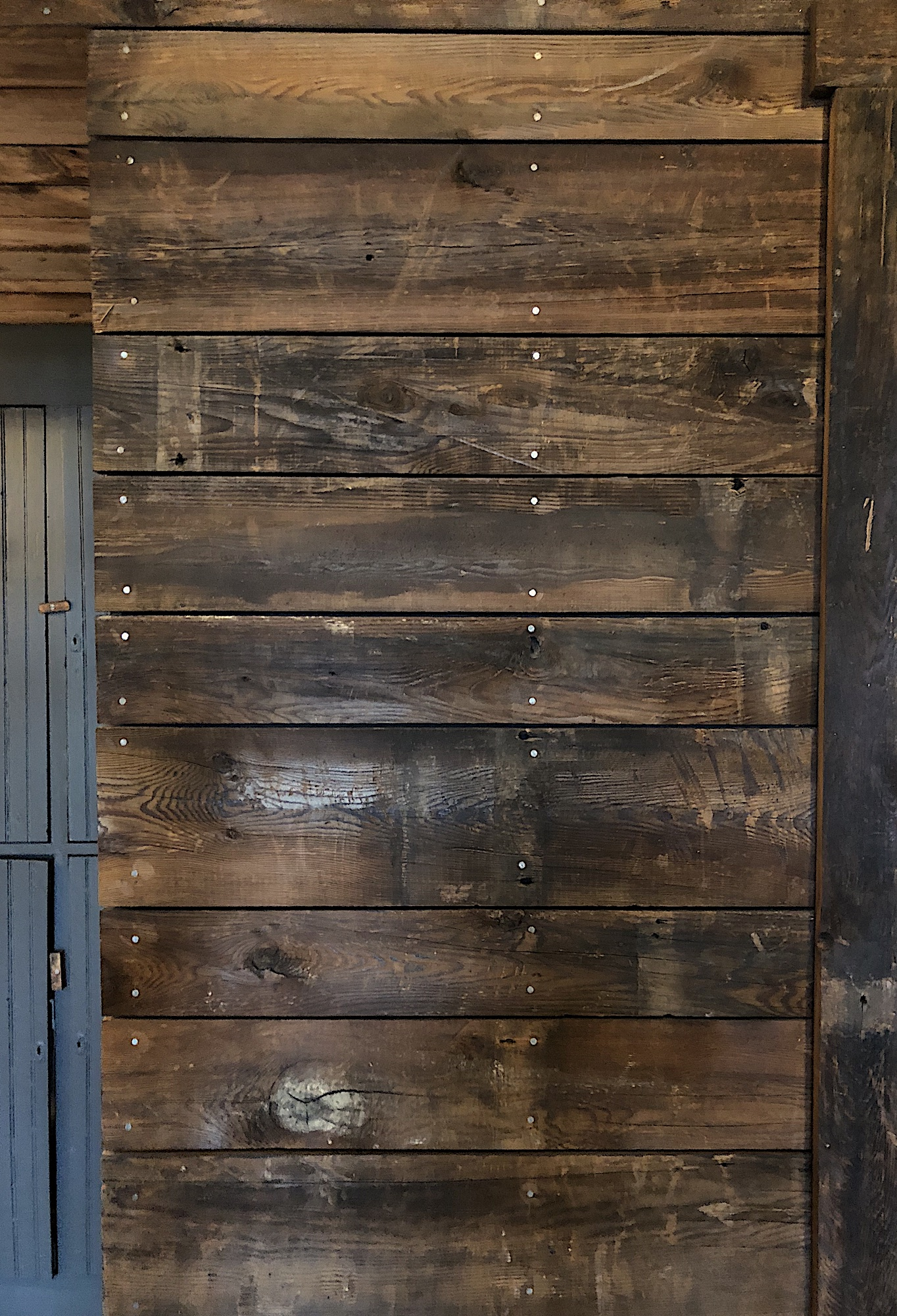Narrow reclaimed barn board wall in a converted barn playhouse in Edgecomb, Maine, sourced by Rousseau Reclaimed Lumber & Flooring