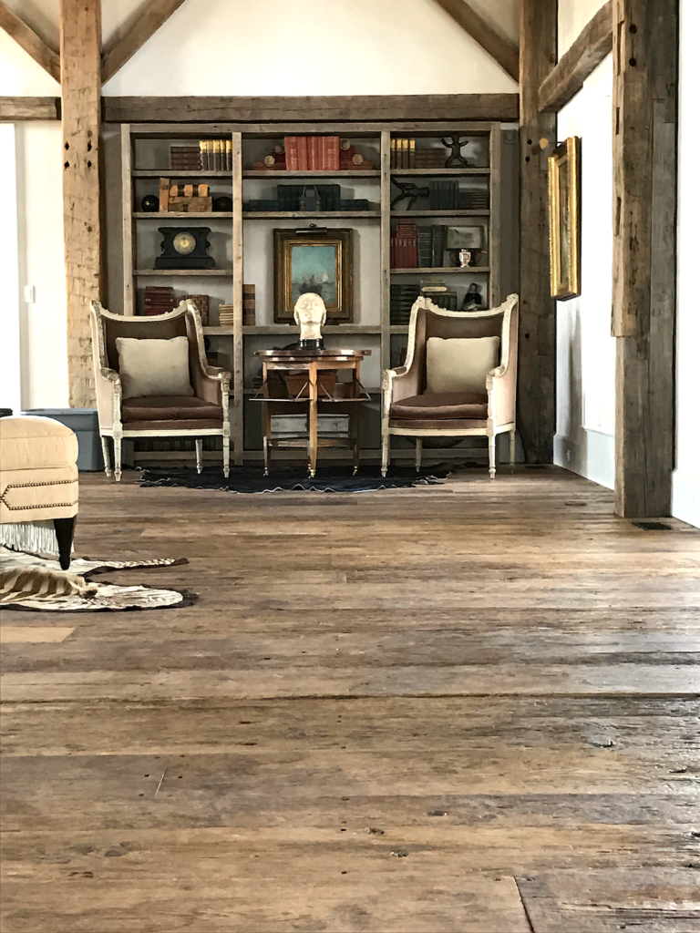 Living room featuring reclaimed threshing floor in a converted barn residence in Pemaquid, Maine